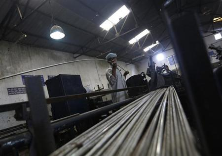 An employee holds a steel rod as he works on the production line inside Hallmark steel factory in Bhiwadi in the desert Indian state of Rajasthan September 30, 2013. REUTERS/Adnan Abidi/Files