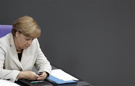 German Chancellor Angela Merkel looks at her mobile phone during a session of the Bundestag, German lower house of parliament, at the Reichstag in Berlin September 12, 2012. REUTERS/Tobias Schwarz/Files