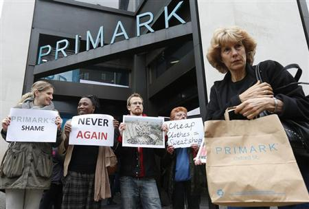 A shopper passes demonstrators outside clothing retailer Primark in central London April 27, 2013. REUTERS/Suzanne Plunkett/Files