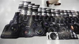 A man walks on an advertisement of Canon digital cameras at an electronics retail store in Tokyo July 24, 2013. Canon Corp снизила прогноз операционной прибыли второй раз за два квартала, отметив снижение продаж дорогих фотокамер в этом году впервые с 2003 года. REUTERS/Issei Kato
