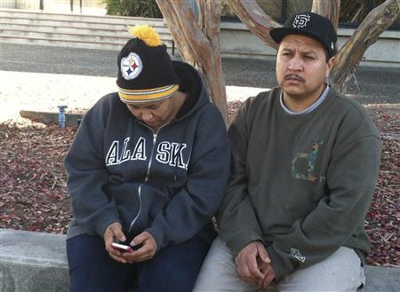 Sujey Cruz, 37, looks at a photograph of her dead son, 13-year-old Andy Lopez Cruz, as she and the boy's father, Rodrigo Lopez, 37, sit outside Santa Rosa City Hall to silently protest the eighth-grader's fatal shooting by a Sonoma County sheriff's deputies in Santa Rosa, California October 23, 2013. REUTERS/Ronnie Cohen