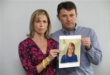 Kate and Gerry McCann pose with a computer generated image of how their missing daughter Madeleine might look now, during a news conference in London May 2, 2012. REUTERS/Andrew Winning