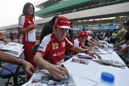 Ferrari Formula One driver Fernando Alonso (front) of Spain signs autographs for fans at the Buddh International Circuit in Greater Noida on the outskirts of New Delhi October 24, 2013. REUTERS/Ahmad Masood
