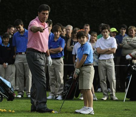 Spanish golfer Jose Maria Olazabal instructs a child during a golf clinic in La Barganiza, near Oviedo, northern Spain October 23, 2013. REUTERS/Eloy Alonso