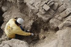Un arqueólogo limpia restos de una tumba de una momia de la cultura Wari en Miraflores, Perú, oct 24 2013. Dos fardos funerarios de unos 1.000 años de antigüedad, con un adulto y un niño adentro, fueron encontrados intactos en un complejo ceremonial preincaico en la capital de Perú, dijo el jueves la arqueóloga a cargo del hallazgo. REUTERS/Mariana Bazo