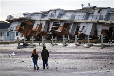 People walk past a beach club destroyed by Hurricane Sandy in Sea Bright, New Jersey, October 31, 2012. REUTERS/Lucas Jackson