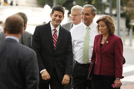U.S. Representative Paul Ryan (R-WI) (L) smiles and talks with fellow House Republicans as they arrive for meetings at the Republican National Committee offices on Capitol Hill in Washington October 23, 2013. REUTERS/Jonathan Ernst