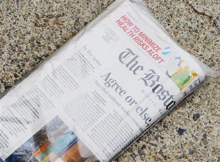 A morning delivery of the Boston Globe newspaper sits on a front porch in Medford, Massachusetts May 4, 2009. REUTERS/Brian Snyder