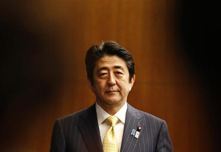 Japan's Prime Minister Shinzo Abe (C) is seen between photographers as he poses for a photograph at the start of a news conference at his official residence in Tokyo June 26, 2013, to mark the end of the ordinary parliamentary session. REUTERS/Toru Hanai