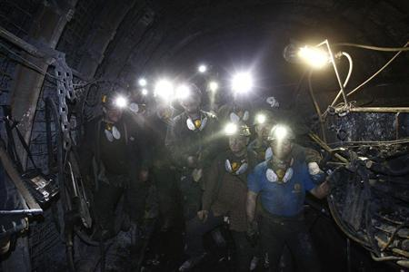 A group of miners pose for a photograph inside of an excavation corridor at Zofiowka coal mine in Jastrzebie Zdroj, southern Poland April 3, 2013. REUTERS/Peter Andrews
