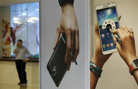 A man talks on his mobile phone near advertisements promoting the Samsung Electronics' Galaxy Note 3 at the company's headquarters in Seoul October 21, 2013. REUTERS/Kim Hong-Ji