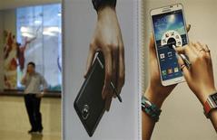 Publicités pour le Galaxy Note 3 de Samsung affichées au siège du groupe à Séoul. Le numéro un mondial des smartphones enregistre un résultat opérationnel record au troisième trimestre. La forte reprise des activités puces mémoire a compensé le net ralentissement de la croissance des ventes de téléphones portables. /Photo prise le 21 octobre 2013/REUTERS/Kim Hong-Ji