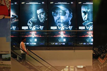 A man rides an escalator past posters of the movie ''Waar'' at the Atrium cinemas in Karachi October 23, 2013. REUTERS/Akhtar Soomro