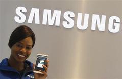 Funcionária da Samsung segura celular em loja de exposição da Samsung em Joanesburgo, 3 de outubro de 2013. O lucro trimestral da Samsung Electronics cresceu 26 por cento para um novo recorde, atingindo expectativas e impulsionado por uma forte recuperação no negócio de chips de memória, enquanto o crescimento das vendas de smartphones enfrenta uma desaceleração. 03/10/2013 REUTERS/Siphiwe Sibeko