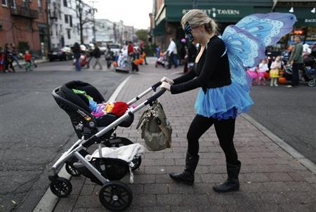 A woman pushes her child in a pram during the annual Ragamuffin Halloween Parade, postponed by Hurricane Sandy, in Hoboken, New Jersey November 12, 2012. REUTERS/Gary Hershorn