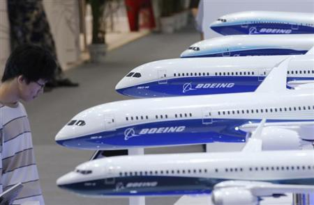 A visitor looks at a display of miniature Boeing passenger aircraft at Aviation Expo China 2013 in Beijing September 25, 2013. REUTERS/Kim Kyung-Hoon