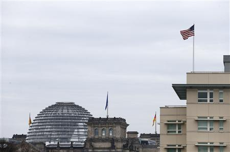 A U.S. flag flies atop the U.S.embassy next to the Reichstag building, seat of the German lower house of parliament Bundestag, in Berlin October 25, 2013. REUTERS-Tobias Schwarz