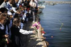 Crianças palestinas jogam flores ao mar no porto de Gaza, em memória aos migrantes palestinos que morreram afogados no Mediterrânio ao tentar a travessia entre a Síria e a Itália. Navios da Marinha e da guarda costeira da Itália resgataram mais de 700 imigrantes nas águas entre a Sicília e o norte da África durante a noite, em mais um incidente da crise imigratória que já custou centenas de vidas neste mês. 23/10/2013 REUTERS/Suhaib Salem
