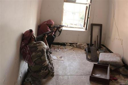 Free Syrian Army fighters take position as they aim their weapons inside a room in Bab Antakya district in Old Aleppo, October 22, 2013. Picture taken October 22, 2013. REUTERS/Molhem Barakat