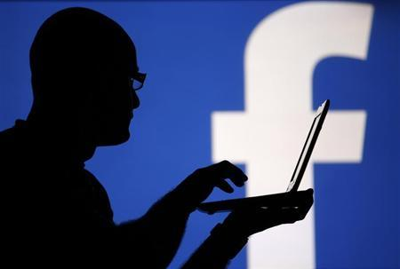 A man is silhouetted against a video screen with an Facebook logo in this photo illustration taken in the central Bosnian town of Zenica, August 14, 2013. REUTERS/Dado Ruvic
