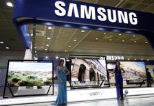 Unas modelos junto a unos televisores de Samsung Electronics en un panel de la firma en Seúl, mayo 22 2013. La ganancia operacional trimestral de Samsung Electronics saltó un 26 por ciento a un nuevo récord, igualando las estimaciones, impulsada por una fuerte recuperación en su negocio de microprocesadores, mientras que el crecimiento de ventas de teléfonos avanzados disminuyó agudamente. REUTERS/Kim Hong-Ji