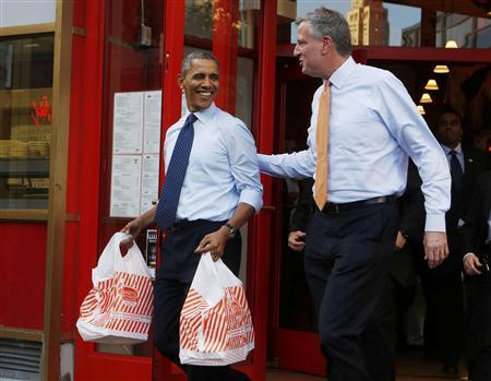 U.S. President Barack Obama walks out with two bags of cheesecake from Junior's Restaurant next to Democratic Mayoral candidate Bill de Blasio in Brooklyn, October 25, 2013. REUTERS/Larry Downing