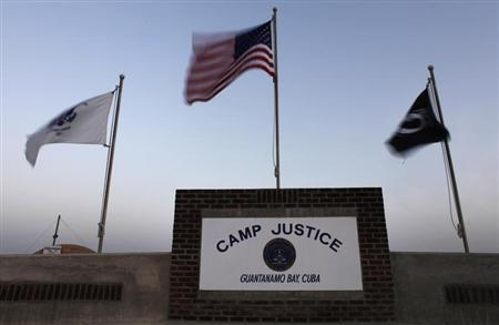 Flags wave above the sign posted at the entrance to Camp Justice, the site of the U.S. war crimes tribunal compound, at Guantanamo Bay U.S. Naval Base in Cuba May 31, 2009. REUTERS/Brennan Linsley/Pool