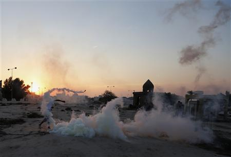 An anti-government protester throws a tear-gas canister, initially fired by riot-police, back at them during clashes after the funeral ritual of visiting the grave of 17-year-old Ali Khalil in the village of Bani Jamra, west of Manama, October 26, 2013. REUTERS/Hamad I Mohammed