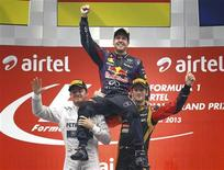 Mercedes Formula One driver Nico Rosberg of Germany (L) and Lotus F1 Formula One driver Romain Grosjean of France (R) lift Red Bull Formula One driver Sebastian Vettel of Germany after the Indian F1 Grand Prix at the Buddh International Circuit in Greater Noida, on the outskirts of New Delhi, October 27, 2013. REUTERS/Adnan Abidi