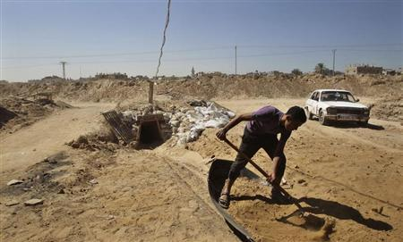 A tunnel worker shovels sand outside a smuggling tunnel on the border between Egypt and the southern Gaza Strip October 8, 2013. REUTERS/Ahmed Zakot