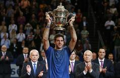 Juan Martin Del Potro (C) of Argentina raises the winner's trophy after he won his final match against Switzerland's Roger Federer at the Swiss Indoors ATP tennis tournament in Basel October 27, 2013. REUTERS/Arnd Wiegmann