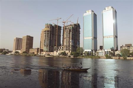 A boat passes buildings under construction and the two towers of the Bank of Egypt building (R), overlooking the river Nile in Cairo June 7, 2013. REUTERS/Asmaa Waguih