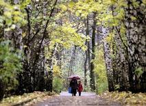 Женщина с ребенком гуляют в московском парке 22 октября 2004 года. Рабочая неделя принесет в Москву небольшое похолодание, ожидают синоптики. REUTERS/Viktor Korotayev