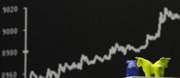 Фигурки быков на фоне табло с графиком динамики индекса DAX на Франкфуртской фондовой бирже 25 октября 2013 года. Европейские акции близки к пятилетнему пику, а немецкий фондовый индекс DAX обновил исторический максимум, благодаря высоким квартальным показателям компаний. REUTERS/Kai Pfaffenbach