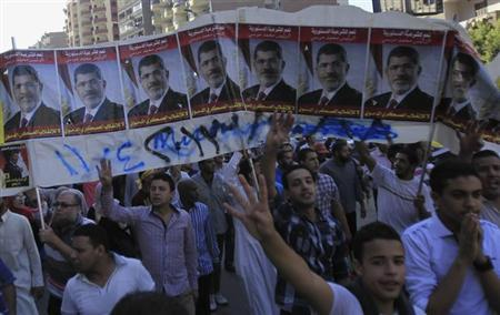 Supporters of the Muslim Brotherhood and ousted Egyptian President Mohamed Mursi shout slogans against the military and interior ministry, while gesturing with four fingers, under Mursi posters, during a protest around Khatem El Morsalien mosque near Giza square, south of Cairo, October 25, 2013. REUTERS/Amr Abdallah Dalsh