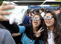 """Children take pictures during an attempt to break a world record for largest gathering of people wearing googly eye glasses (also know as slinky eyes or droopy eye) at a Halloween party at an after school center called """"A Place Called Home"""" in Los Angeles, California, October 25, 2013. REUTERS/Kevork Djansezian"""