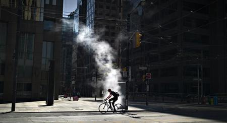 A cyclist passes a steam vent on the empty streets of the financial district during the annual Victoria Day holiday in Toronto, Ontario May 20, 2013. REUTERS/Andy Clark