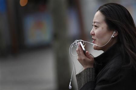 A woman speaks on her smartphone as she walks on a busy street in downtown Shanghai in this March 13, 2013 file photo. REUTERS/Carlos Barria
