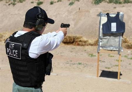 An ATF agent fires rounds from an FN 5.7 Herstal pistol, better known on the streets as a ''Cop Killer'' weapon, at a body armor vest during a demonstration of the firepower of weapons commonly used by criminals along the U.S.-Mexico at the Ben Avery Shooting Range in Phoenix, Arizona, March 10, 2008. REUTERS/Rick Scuteri