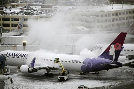 A Hawaiian Airlines plane, delayed for approximately 4 hours, undergoes de-icing before takeoff at Seattle-Tacoma International Airport in Seatac, Washington January 19, 2012. REUTERS/Cliff DesPeaux