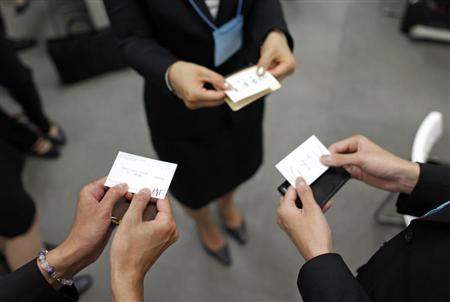 Japanese job-hunting students dressed in suits practice swapping business cards during a business manners seminar at a placement centre in Tokyo May 28, 2012. REUTERS/Toru Hanai