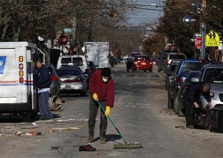 A Midland Beach resident sweeps debris in a street at Staten Island in New York November 14, 2012. REUTERS/Brendan McDermid