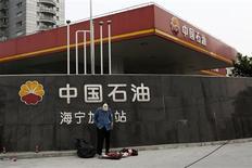 Un recolector de basura junto a una gasolinera de Petrochina en Shanghái, sep 9 2013. Las mayores petroleras estatales de China, que poseen antiguos yacimientos, están luchando por elevar la producción de crudo y gas natural para cubrir la creciente demanda local a través de una serie de inversiones con las que también arriesgan un incremento en sus costos. REUTERS/Aly Song