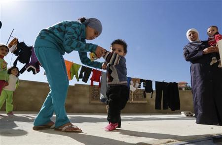 A Syrian refugee girl helps her brother, who the family suspects has polio, to walk as their mother watches in a mosque compound in Shebaa area, southern Lebanon October 28, 2013. REUTERS/ Jamal Saidi