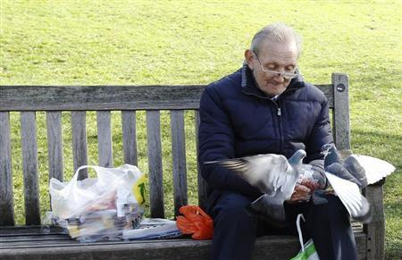 An elderly man feeds pigeons in St James's Park in London March 8, 2012. REUTERS/Luke MacGregor