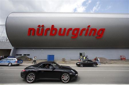 A car passes the newly built event centre of the Nuerburgring race course July 9, 2009. REUTERS/Johannes Eisele