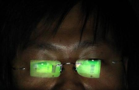 A hacker, who requests not to have his name revealed, works on his laptop in his office in Taipei July 10, 2013. REUTERS/Pichi Chuang