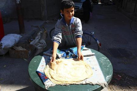 A boy makes bread in Duma neighbourhood, in Damascus September 22, 2013. All official government bakeries were closed since 10 months ago and no flour has reached the area except those smuggled by Free Syrian army members, activists said. REUTERS/Bassam Khabieh