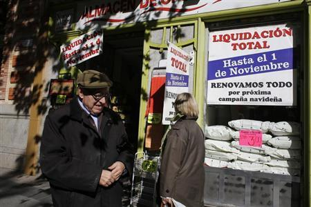 People walk past a shop in Madrid October 29, 2013. REUTERS/Juan Medina