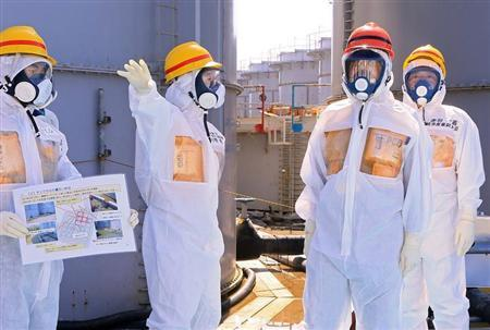 Japan's Prime Minister Shinzo Abe (2nd R), wearing protective suit and mask, is briefed about tanks containing radioactive water by Fukushima Daiichi nuclear power plant chief Akira Ono (2nd L), as they stand near a tank (C, with railings painted red and blue) which is being dismantled after leaking contaminated water, during his inspection tour to the Tokyo Electric Power Co. (TEPCO)'s tsunami-crippled Fukushima Daiichi nuclear power plant in Okuma, Fukushima Prefecture, September 19, 2013. REUTERS/Pool